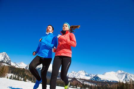 personas trotando: Pareja joven que activa al aire libre en las montañas soleados de invierno