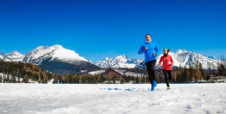 freddo: Coppia giovane jogging esterno in sole montagne di inverno Archivio Fotografico