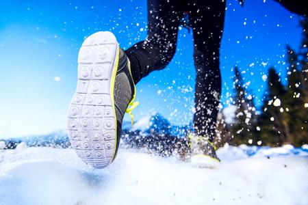 invierno: Las piernas de un joven corredor de afuera en la naturaleza de invierno