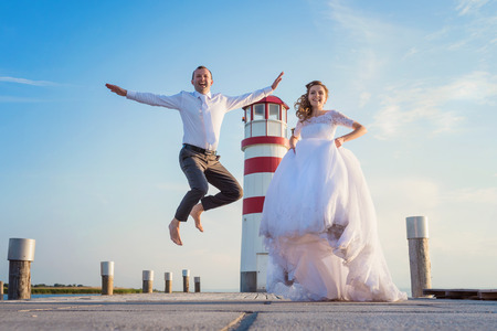 Beautiful young wedding couple on the pier in front of lighthouse photo