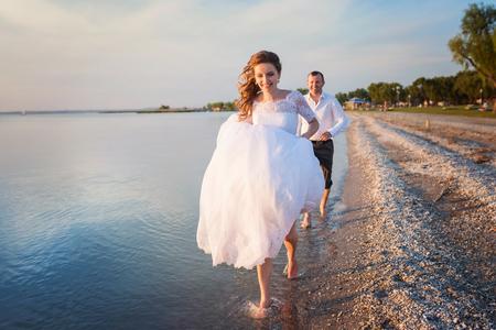 Mooie jonge bruidspaar bij de kust