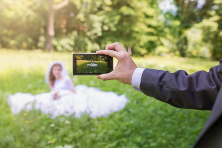 Beautiful young wedding couple taking pictures in a park photo