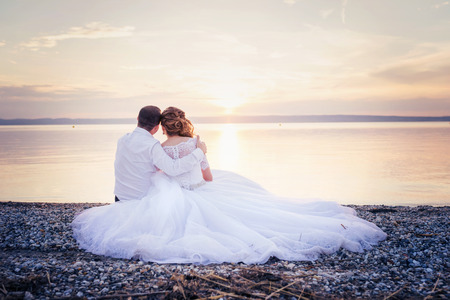 lake beach: Beautiful young wedding couple at the shore