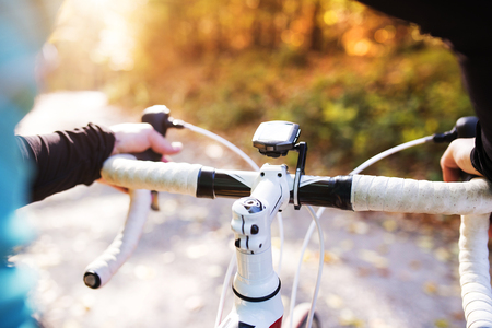 road cycling: Young handsome sportsman riding his bicycle outside in sunny autumn nature