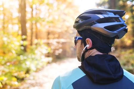 sportsman: Deportista guapo joven que monta su bicicleta fuera en la naturaleza soleada de otoño