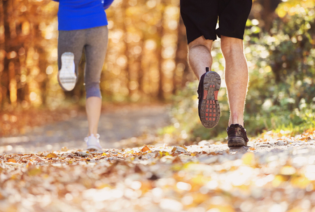 Beautiful couple running outside in autumn nature