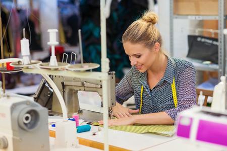 coser: Jóvenes hermosas ropas mujer de coser con la máquina de coser.