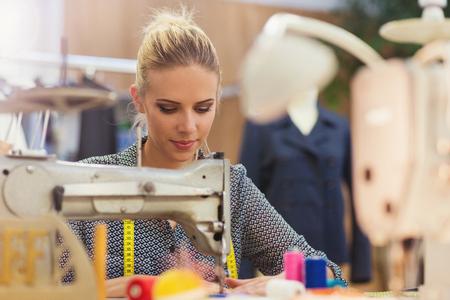 Mooie jonge vrouw het naaien van kleding met een naaimachine.