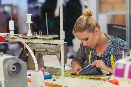 年輕漂亮的女人縫衣服用縫紉機。
