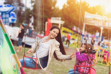 chain swing ride: Cute little girl with her mum having fun at fun fair