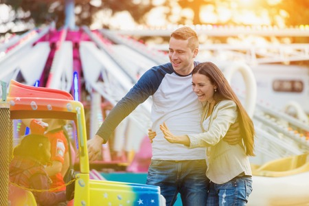 Família nova bonita que aprecia seu tempo no parque de diversões