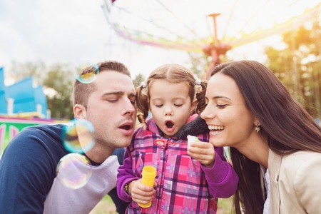 familie: Schöne junge Familie genießen ihre Zeit bei Kirmes Lizenzfreie Bilder