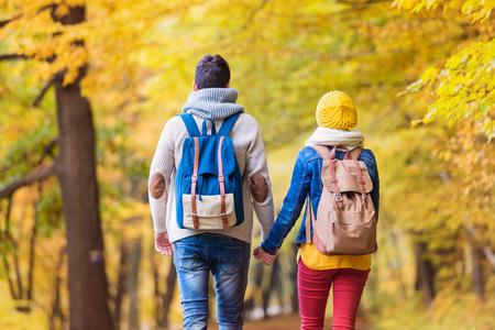 niño con mochila: Hermosa joven pareja en una caminata en el bosque de otoño