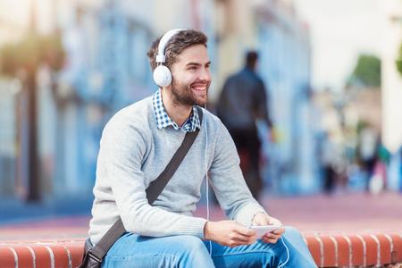 personas escuchando: Apuesto joven con auriculares blancos fuera de la ciudad