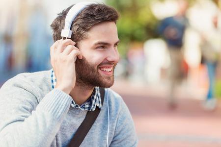 auriculares: Apuesto joven con auriculares blancos fuera de la ciudad