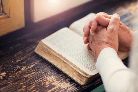 personas orando: Mujer irreconocible que sostiene una biblia en sus manos y la oración Foto de archivo