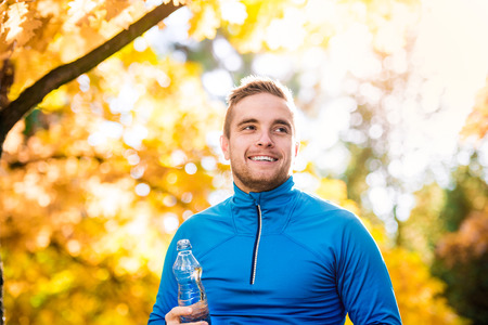 active lifestyle: Young handsome runner outside in sunny autumn nature