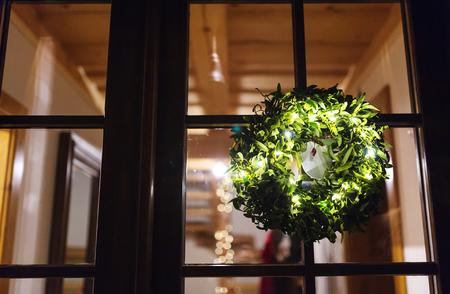 muerdago: corona de mu�rdago verde colgar en la puerta de cristal Foto de archivo