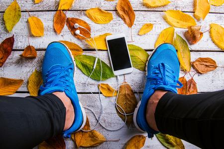 hombre deportista: corredor irreconocible con el teléfono inteligente. Estudio tirado en el fondo de madera.