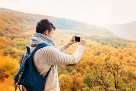 people and nature: Handsome young man taking picture in autumn forest