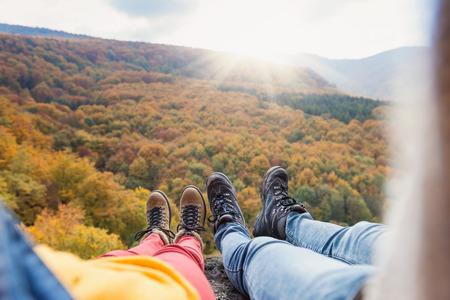 Non reconnaissable jeune couple lors d'une randonnée dans la forêt d'automne