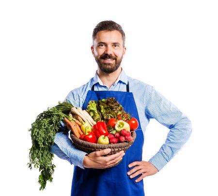 delantal: Jardinero hermoso joven en delantal azul. Estudio tirado en el fondo blanco