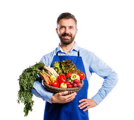 apron: Young handsome gardener in blue apron. Studio shot on white background Stock Photo