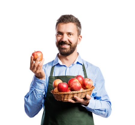 a hobby: Young handsome gardener holding a basket full of apples. Studio shot on white background