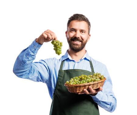 harvest basket: Young handsome gardener holding a basket full of grapes. Studio shot on white background