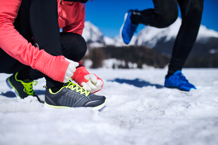 cross ties: Young couple jogging outside in sunny winter mountains