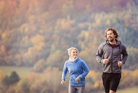 active lifestyle: Beautiful couple running outside in sunny nature