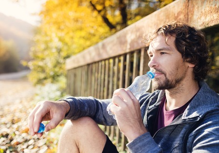 man drinking water: Young handsome runner with water bottle sitting on a bridge Stock Photo