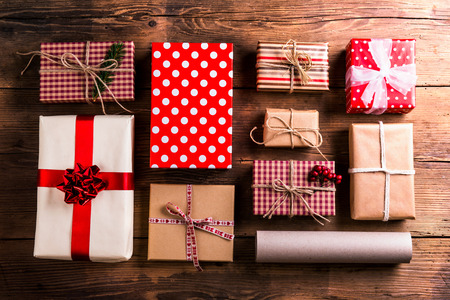 Christmas presents laid on a wooden table background Archivio Fotografico