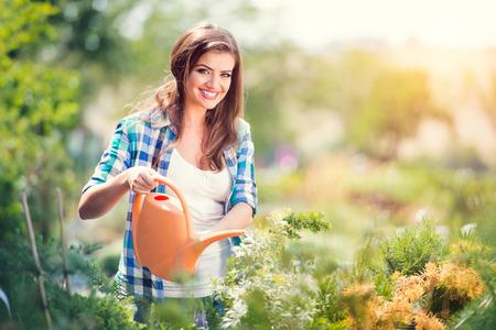 jardinero: Mujer joven hermosa jardinería exterior en naturaleza del verano