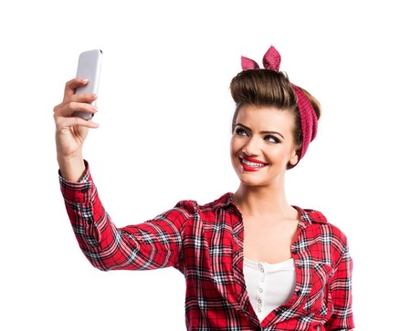 smartphone: Beautiful young woman with pin-up make-up and hairstyle. Studio shot on white background Stock Photo