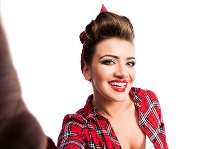 photo studio: Beautiful young woman with pin-up make-up and hairstyle. Studio shot on white background Stock Photo