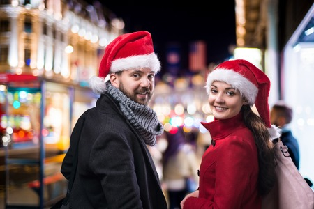 santa hat: Young beautiful couple with Santa hats in the city