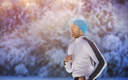 white winter: Handsome young runner in snowy winter nature Stock Photo