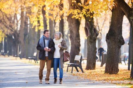 persona caminando: Mayores activos en una caminata en la ciudad de otoño