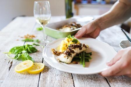 lunch: El hombre que sirve filetes de pescado lucioperca en un plato
