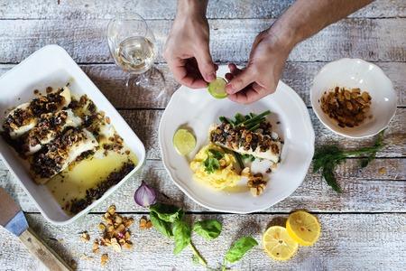 plato de pescado: El hombre que sirve filetes de pescado lucioperca en un plato