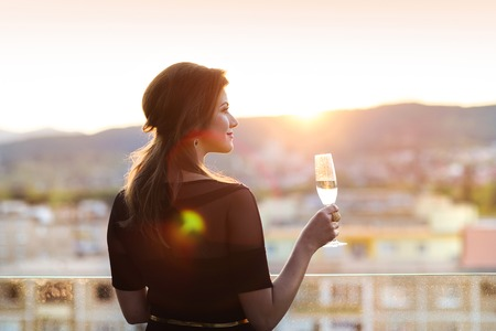 sunshine: Attractive young woman with a drink on a terrace of a bar Stock Photo