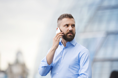 busy beard: Handsome young man with smartphone in the streets of London Stock Photo
