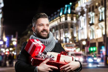 Hombre hermoso joven con los regalos de Navidad en la ciudad