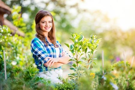 brunet: Beautiful young woman gardening outside in summer nature
