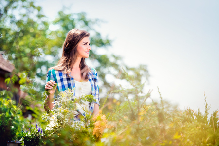 plant hand: Beautiful young woman gardening outside in summer nature