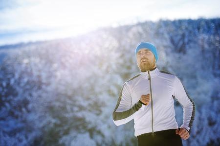 hombre deportista: Corredor joven hermoso en la naturaleza de invierno cubierto de nieve