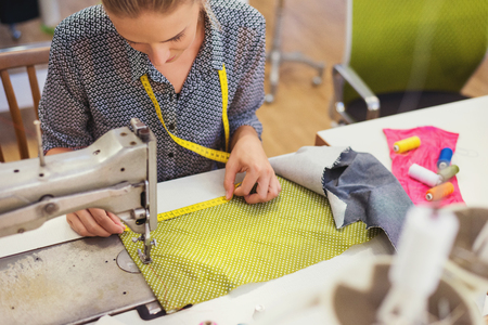 재봉틀 아름다운 젊은 여자와 바느질 옷.