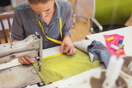 Mooie jonge vrouw naaien kleren met naaimachine.