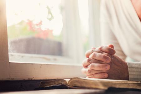 personas orando: Manos de una mujer irreconocible con la biblia orando